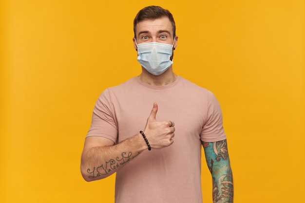 Happy young tattooed bearded man in pink tshirt and hygienic mask to prevent infection looks confident and showing thumbs up gesture over yellow wall