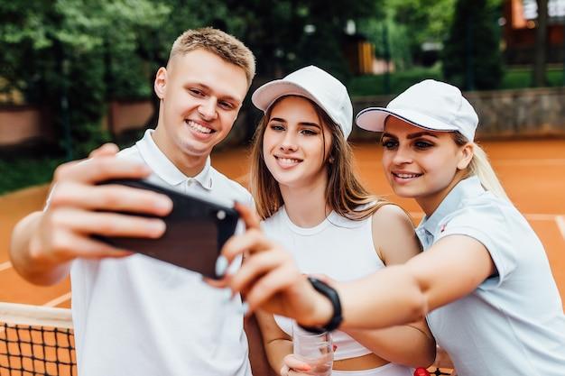 コートでテニスをした後の幸せな若いチーム。電話で写真を撮る水と笑顔の若い男と美しい女性の肖像画。