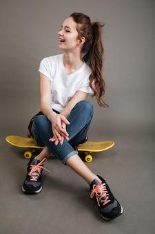 Счастливая молодая девушка сидит на скейтборде и смеется