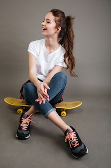 Happy young teenage girl sitting on skateboard and laughing