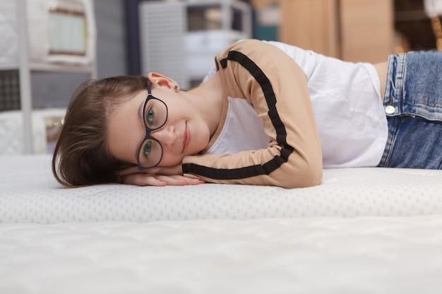 Happy young teenage girl smiling lying on a new orthopedic bed