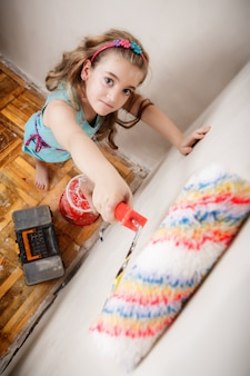 Happy young teenager girl is painting a wall in her room