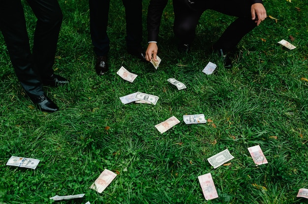 幸せな若い3人のビジネスマンは、お金の雨の下で自然の上に立ってリラックスし、ドル紙幣の現金が落ちています。お金の獲得と喪失。飛び去るドル紙幣。