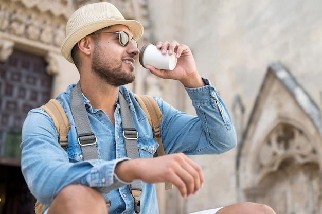 Счастливый молодой турист человек с кофе, чтобы пойти и рюкзак, отдыхая на улице