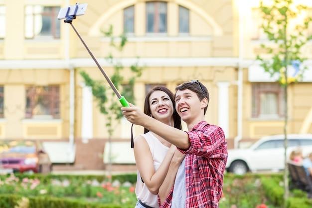 街のモノポッドでスマートフォンで自分撮りをしている幸せな若い観光客のカップルは男です