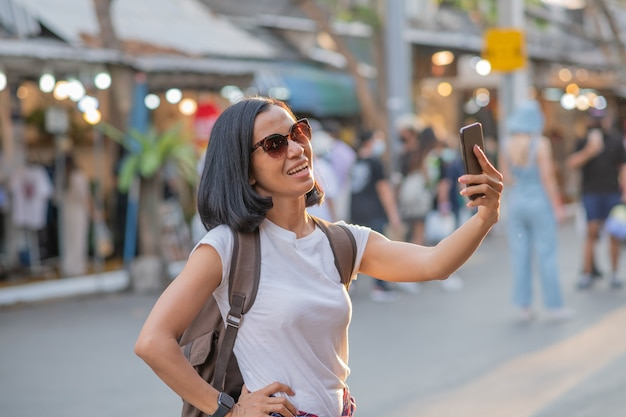 Happy young travel asian woman using mobile phone and relax on street.