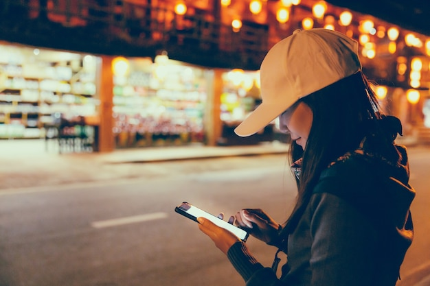 Happy young traveler asian woman using mobile phone on shopping street night market with light bulb bokeh background at night in thailand, travel vacation city concept