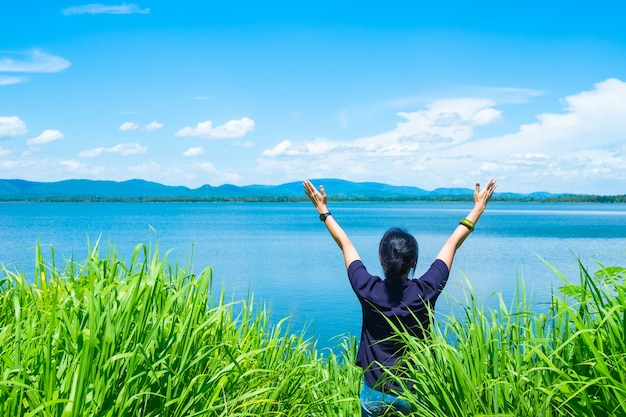 Happy young traveler woman raised arm up to sky enjoying a beautiful of nature at top of mountain