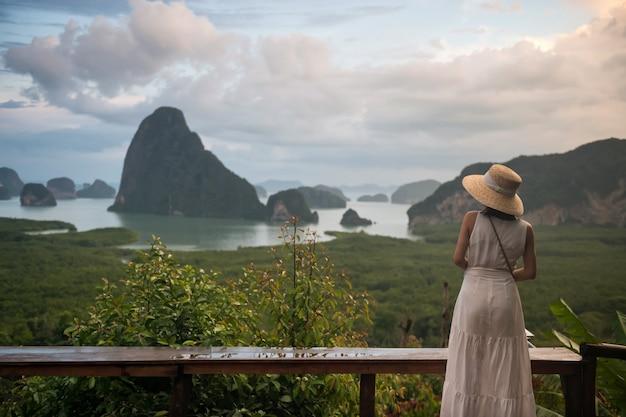 帽子をかぶった幸せな若い旅行者の女性は、タイのパンガーにあるサメドナンチーの視点から自然の美しさを楽しんでいます。アンタマン海のジェームボンド島の海景をご覧ください。