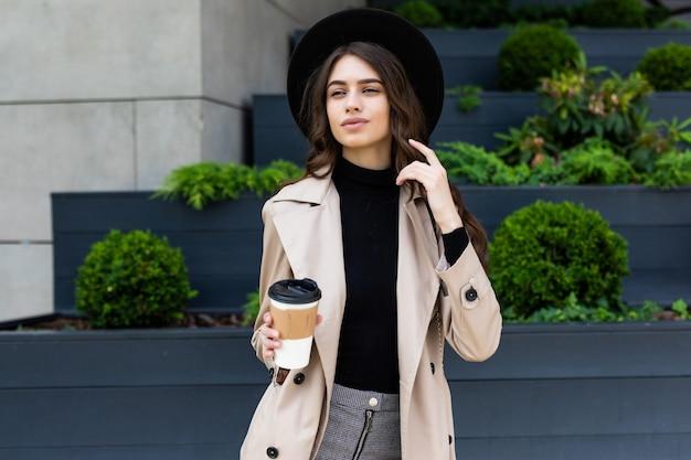 행복 한 젊은 유행 여자 마시는 커피를 빼앗아 도시 도시에서 쇼핑 후 산책