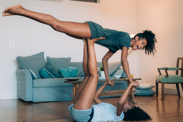 Happy young two black women relaxed at home playing