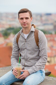 Happy young urban man drinking coffee  european city outdoors