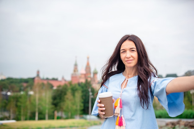 Happy young urban woman drinking coffee in european city.