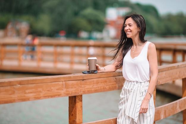 Кофе счастливой молодой городской женщины выпивая в европейском городе.