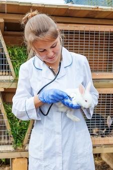 청진기를 들고 목장에서 토끼를 검사 행복 젊은 수의사 여자