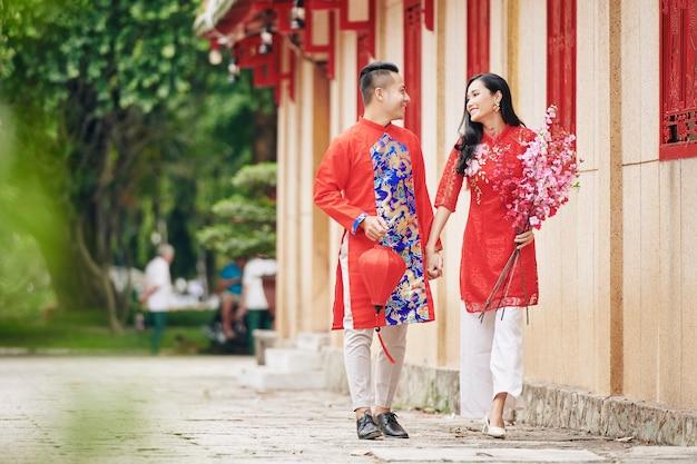 거리를 걸을 때 손을 잡고 실크 랜턴과 꽃이 만발한 복숭아 가지를 가진 행복한 젊은 베트남 남자 친구와 여자 친구