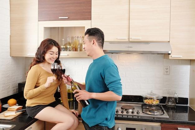 Valntines의 날 저녁 식사를 요리할 때 부엌 카운터에서 와인을 마시는 행복한 젊은 베트남 커플