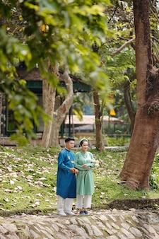 아오자이 드레스를 입은 행복한 젊은 베트남 커플은 행사 후 하루를 함께 보내는 도시 공원의 연못 물을 바라보고 있습니다