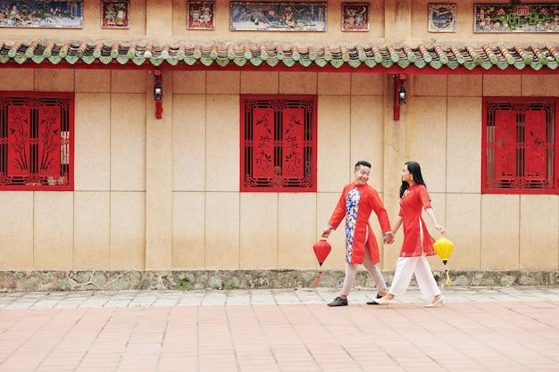 手をつないで、手に絹の灯籠を持って通りを歩く伝統的なドレスを着た幸せな若いベトナム人カップル