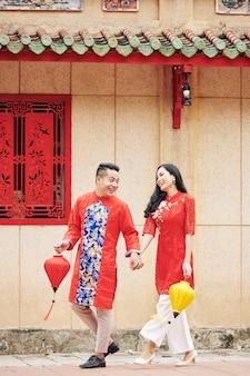 通りを歩いてお互いを見ながら手に絹のランタンと伝統的なドレスを着た幸せな若いベトナム人カップル