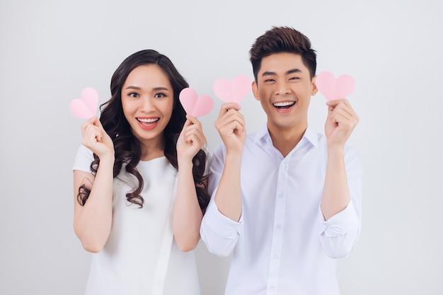 幸せな若いベトナムのカップルはピンクの紙の心を持って笑っています