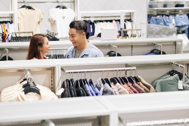 백화점에서 옷의 섬을 따라 걷는 행복 한 젊은 베트남 커플