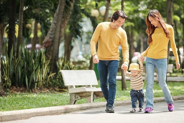 晴れた日に公園を歩いている幼い息子と幸せな若いベトナムの家族