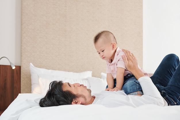 Счастливый молодой вьетнамский отец с годовалым сыном, играя дома на кровати