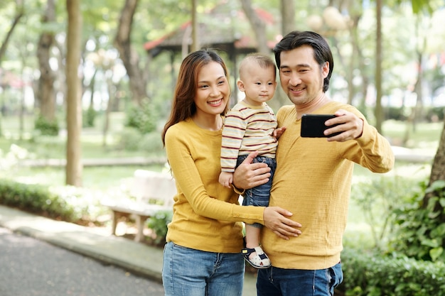 公園を歩いているときに妻と幼い息子と自分撮りを話している幸せな若いベトナム人男性