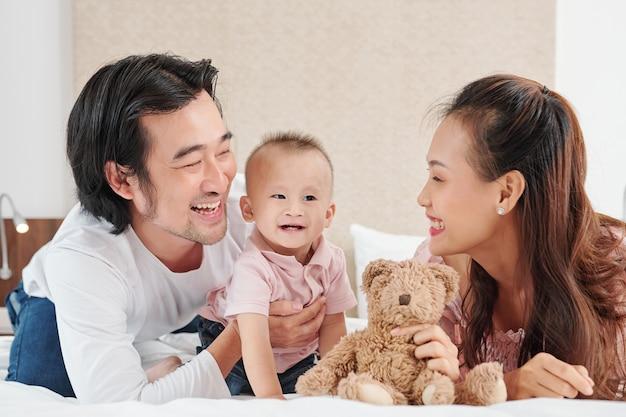 Счастливые молодые вьетнамские мать и отец играют с маленьким сыном в спальне