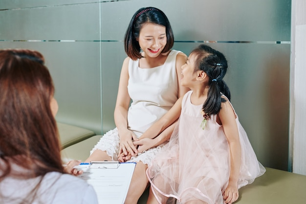 Happy young vietnamese mother and daughter visiting pediatrician in hospital