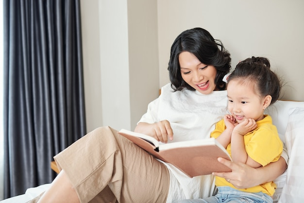 Happy young vietnamese woman reading a book with fairytales for her little daughter when they are sitting on bed