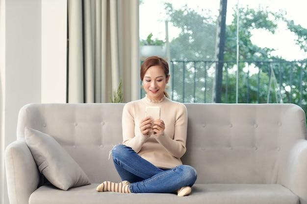 Счастливая молодая вьетнамская женщина расслабляется в гостиной, просматривает беспроводной интернет на мобильном устройстве.