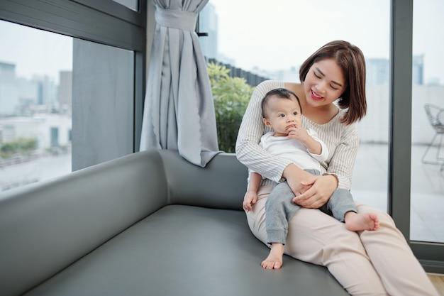 彼女の膝の上に赤ちゃんと一緒にソファに座っている幸せな若いベトナム人女性