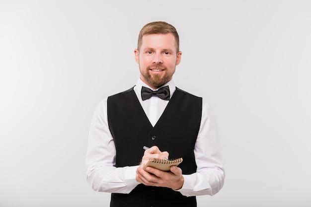 Счастливый молодой официант в черном жилете и галстуке-бабочке записывает ваш заказ в блокноте, стоя перед камерой в изоляции
