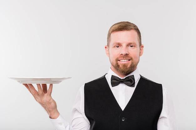 Счастливый молодой официант в галстуке-бабочке и черном жилете держит белую чистую пустую фарфоровую тарелку для гостя ресторана