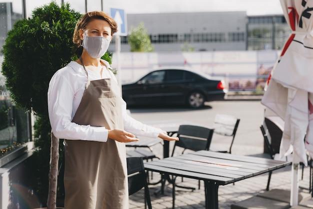 카페 근처에서 제복을 입은 행복한 젊은 웨이트리스가 입구를 가리킵니다. 환영하다.
