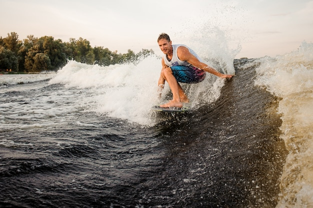 Happy young wakesurfer riding down the river on board