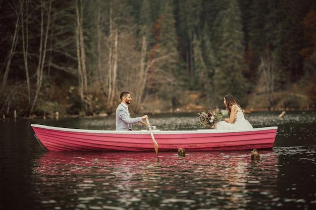 Счастливая молодая свадебная пара на лодке