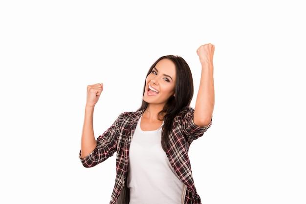 Счастливая молодая женщина достигла своей цели и показывает кулаки