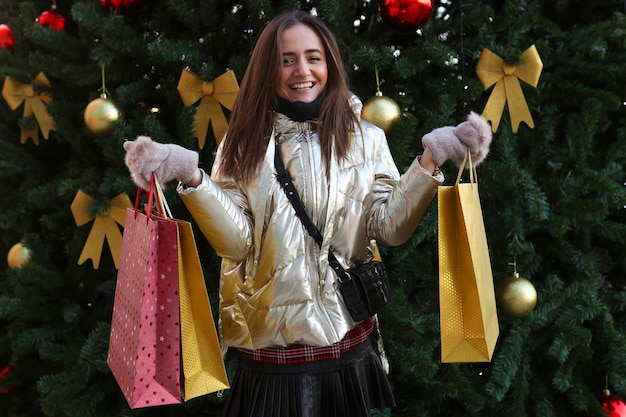 Счастливая молодая женщина после покупок на фоне елки