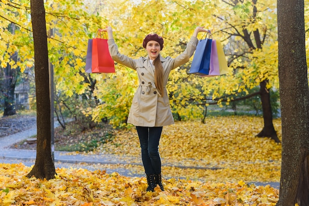 Happy young woman after shopping walks in park