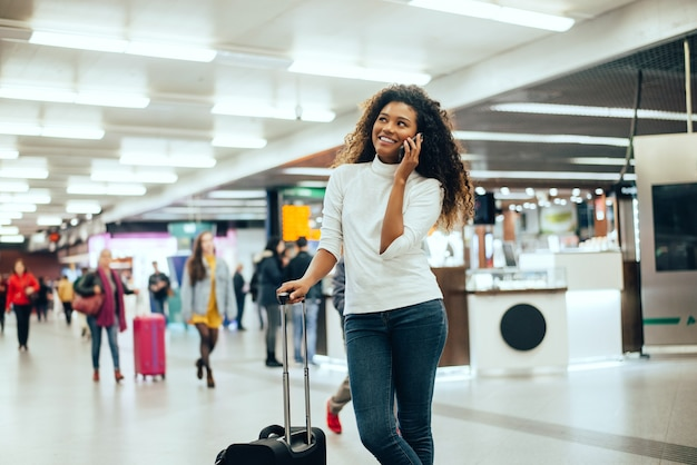 Happy young woman at airport talking on phone.