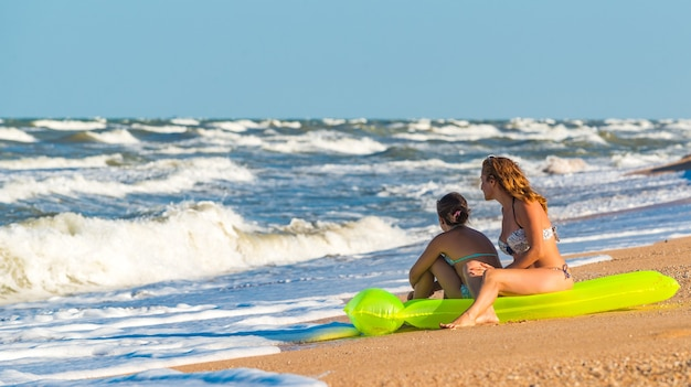 幸せな若い女性と彼女の娘は、海岸の緑のエアマットレスに座って、休暇中の晴れた夏の日に嵐の海の波を待っています。旅行とレジャーの概念。