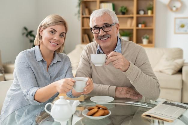 幸せな若い女性と引退した父親がクッキーとティーポットを添えてテーブルの上にお茶のカップを置く