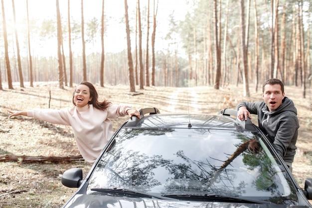 幸せな若い女と男が車の窓から登った。森の中を車で旅行。カントリートリップ。車での休暇