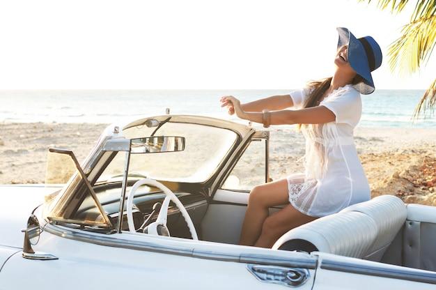 Счастливая молодая женщина и ретро-кабриолет рядом с пляжем в городе варадеро