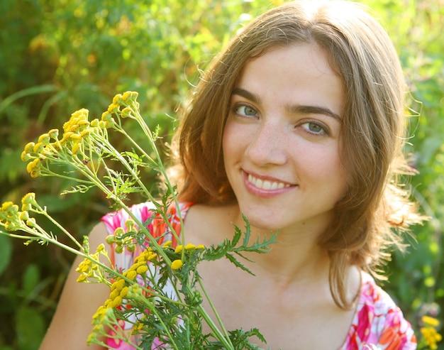 幸せな若い女性と野生の花。