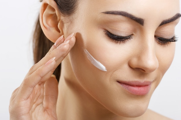 Happy young woman applying cream to her face skincare and cosmetics concept