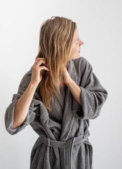 Счастливая молодая женщина, применяя маску для волос в ванной комнате